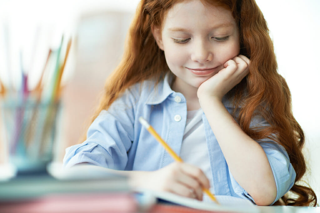 Cute little girl drawing at lesson and smiling