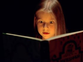 Little girl reading a book, with fear in his eyes